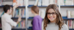 A woman smiling directly at the camera in a library.