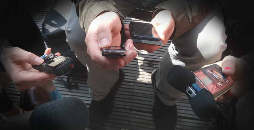 The centre of a journalism scrum. The photo is of many hands holding various kinds of recording devices around the photo taker.