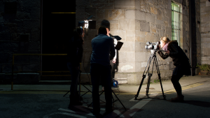 A female journalist at a camera filming an interview subject who is obscured by the lighting techs.