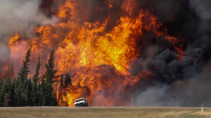 A white truck drives away from a sky of flames during the fires in Fort McMurray