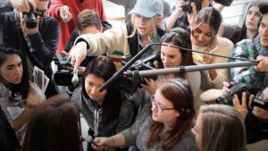 Mostly female journalists scrum interviewing someone. Only the interviewees hair can be seen from behind.
