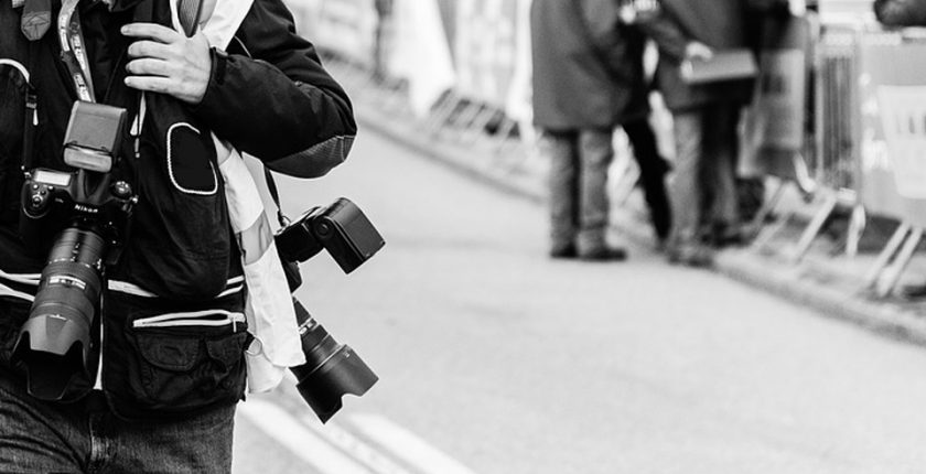 A photographer walking down the street.