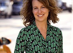 Head shot of Lisa Taylor in a green patterned dress.