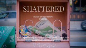 """Movie poster for the documentary Shattered. An abandoned newspaper box with a free metro paper in it alongside garbage. The title """"Shattered"""" is framed by the newspaper box."""