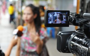 A woman is being interviewed out of focus in the background. A camera is set up and filming the woman. There is an in focus shot of her in the view finder.