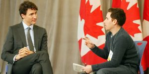 Justin Trudeau being interviewed by a journalists with Canadian flags in the background.